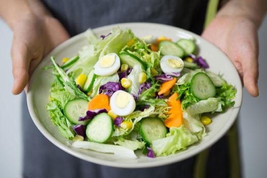 Persona che mostra un piatto di insalata